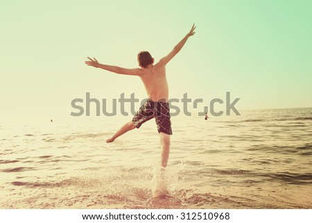 Boy jumping  into the waves of a lake. Instagram effect.