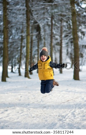 boy jumping up in the winter forest