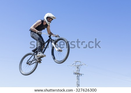 boy jumping with BMX bike on a BMX session in the mountain - focus on the leg - stock photo