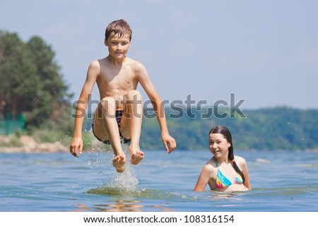 Boy jumping with girl, two children playing in water - stock photo