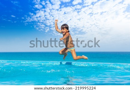 Boy jumps in swimming pool with seaside background - stock photo