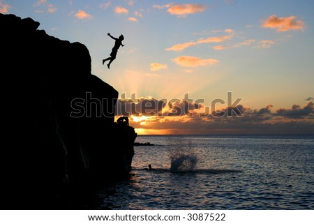 Boy jumps off a cliff into the ocean at Waimea Bay in Hawaii at sunset. - stock photo
