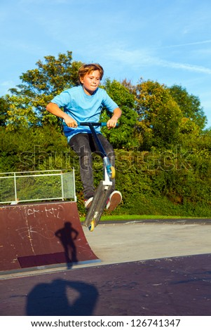 boy jumps with scooter at the skate park over a ramp and has fun