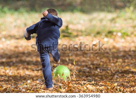 boy kicking ball in autumn leaves - stock photo