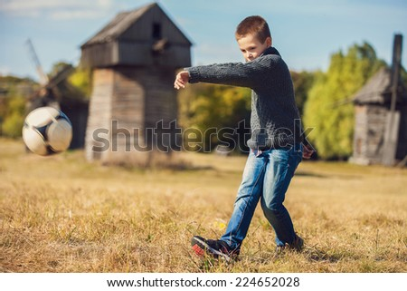 boy kicking ball in the grass outdoors - stock photo