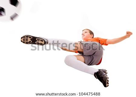 Boy kicking soccer ball, isolated on white - stock photo