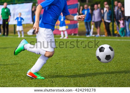 Boy kicking soccer ball on sports field. Soccer football training session for children, teens - stock photo