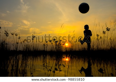 Boy kicks the ball during sunset - stock photo