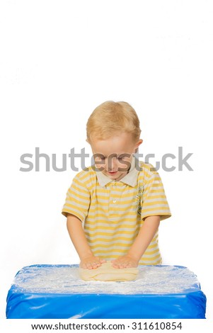 Boy knead the dough by hand for making a cake on a blue