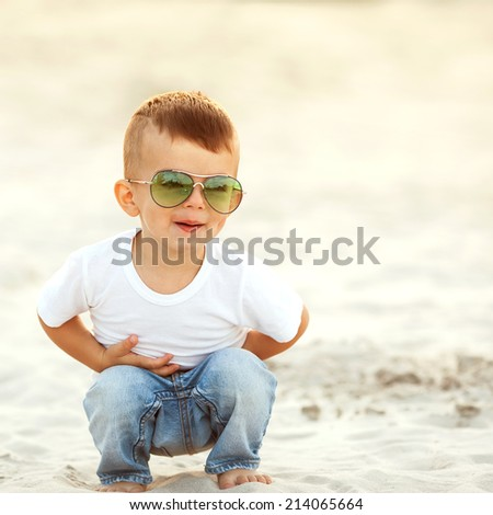 boy laughing in the sand, walking along the beach - stock photo