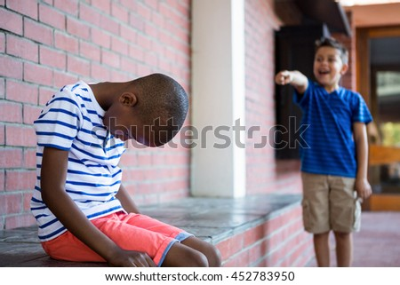 Boy laughing on sad classmate in corridor at school - stock photo