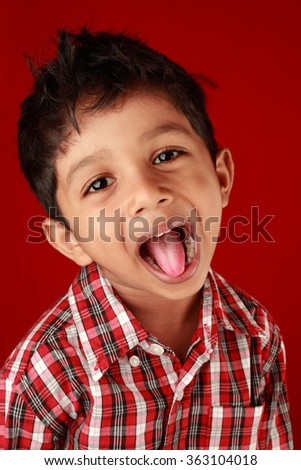 Boy laughs with his tongue out in a red background - stock photo