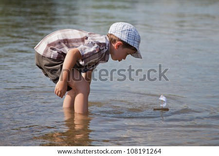 Boy launches  a small sailboat in the river