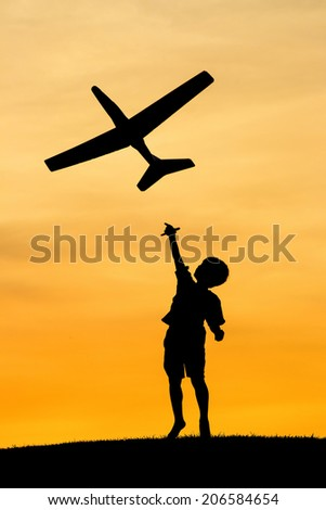 Boy launches toy plane. - stock photo