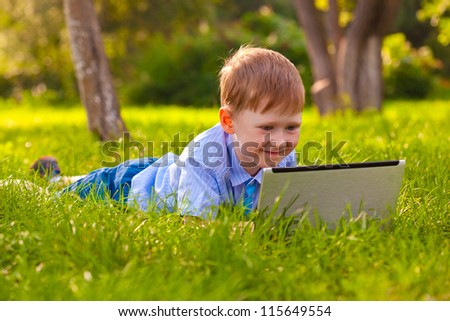 boy laying on green grass in the park with laptop