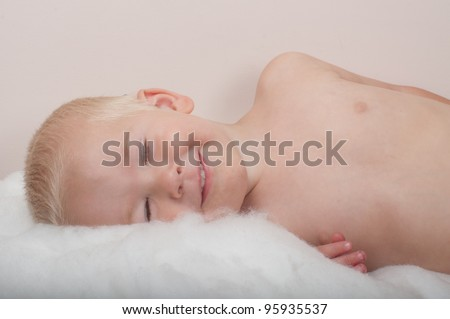 boy laying with eyes closed and big smile