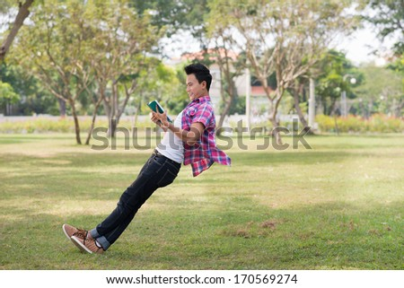 Boy leaning against the air with a book - stock photo