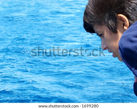 Boy Leaning over Rail of boat - stock photo