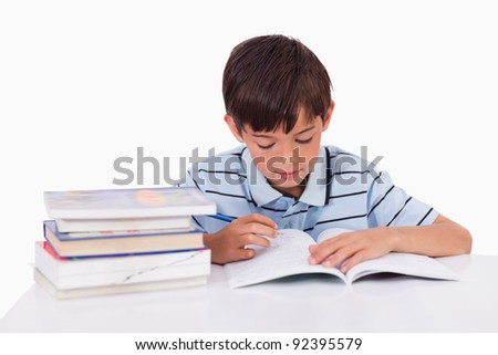 Boy learning his lessons against a white background - stock photo