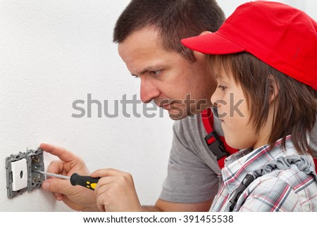 Boy learning how to fix an electrical wall fixture - assisting his father - stock photo