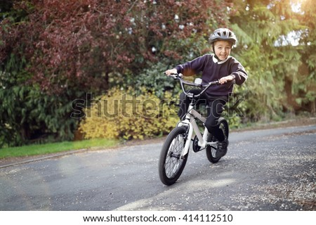 Boy learning to ride his bike home from school - stock photo