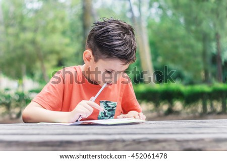 Boy learns to read and write at the park. Summer school holidays, improve knowledge. - stock photo