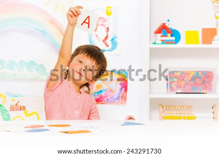 Boy learns to read showing letter card - stock photo