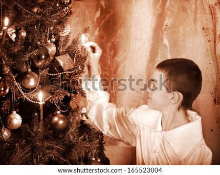 Boy lights candles on  Christmas tree. Black and white retro. - stock photo