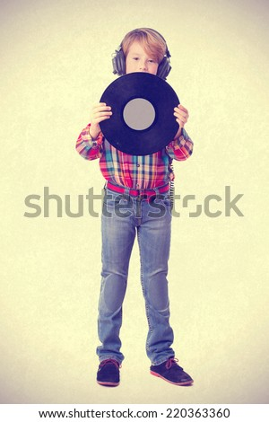 Boy listening music with an headphones and holding a vinyl - stock photo