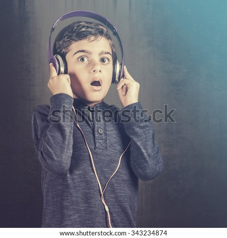 Boy listening to his favorite song. Cross processed image with shallow depth of field - stock photo