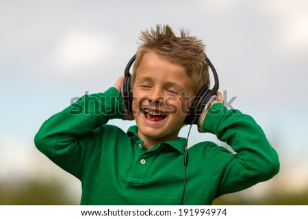 Boy listening to music and singing along. Trademarks have been removed. - stock photo