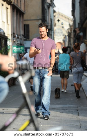 boy listening to music with mp3 walking around the city