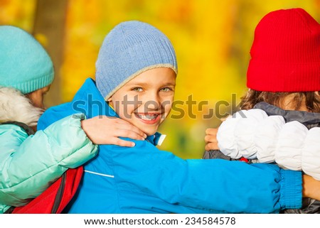 Boy look back with his friends hugging close - stock photo