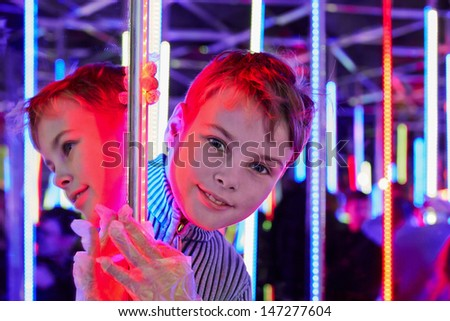 Boy look out from corner in mirror labyrinth - stock photo