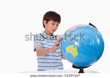 Boy looking at a globe against a white background - stock photo