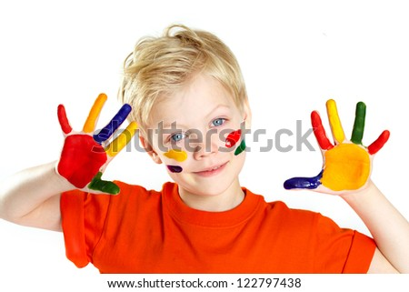 Boy looking at camera with his palms and face covered with paint - stock photo