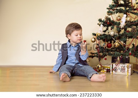 Boy looking at christmas ball in front of christmas tree - stock photo