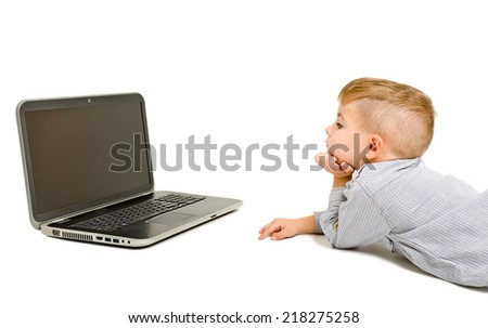 Boy looking at laptop lying on the floor - stock photo