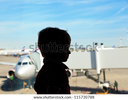 Boy looking at planes in the airport - stock photo