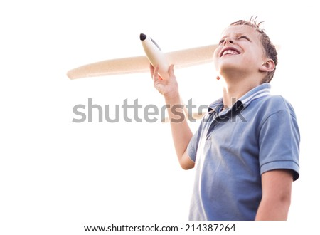 Boy looking at the sky with a plane - stock photo