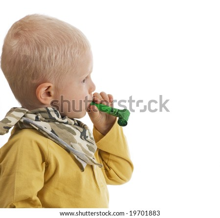 boy looking at viewer blowing noisemaker