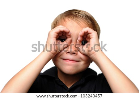 Boy Looking at Viewer Through Hands. Six-year-old boy looking through his hands as if they are binoculars.