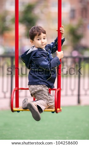Boy looking back climbs on swing on playground - stock photo