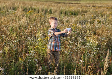 boy looking in smart phone in nature