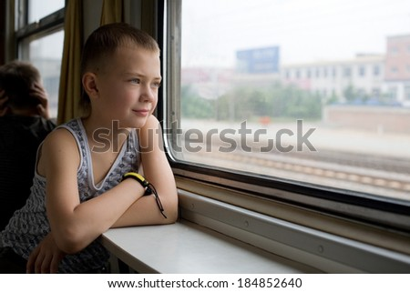 Boy looking out the window on a moving train. - stock photo