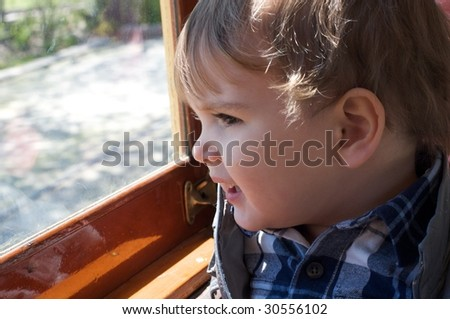 Boy looking out window - stock photo