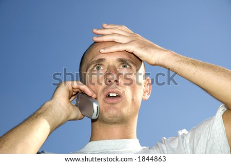 Boy looking surprised on the phone - stock photo