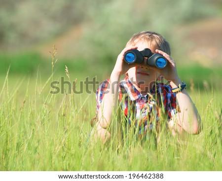 Boy looking through the binoculars - stock photo