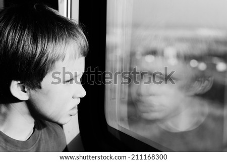 Boy looking through the window - stock photo