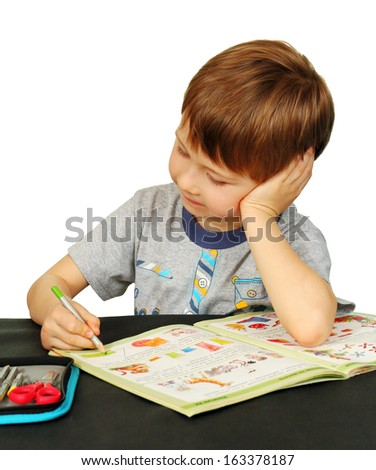 boy looks at an open book lying on the table, white background.